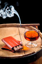 Glass of cognac and cigar on old barrel closeup Stock Images