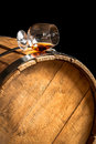 Glass of cognac on the old wooden barrel closeup Stock Photos