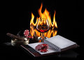 Glass of cognac with poker markers notebook and cigar in fire f flame on black background Royalty Free Stock Image