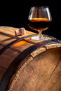 Glass of cognac on the vintage wooden barrel closeup Stock Images