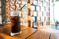 Glass of cola with ice on wood table on a hot day os Summer Royalty Free Stock Photo