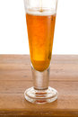Glass of cold golden beer on wooden bar Stock Images