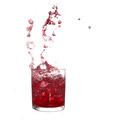 Glass of cold red fruity drink with water splash and ice cubes. Royalty Free Stock Photo