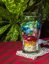 Glass cup with colored buttons buttonsmulti laid in layers in a association joy positive rainbow Royalty Free Stock Photos