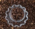 Glass cup on saucer with coffee beans on wooden table view from above Royalty Free Stock Photo