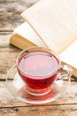 Glass cup of tea with open book on old wooden table hot Stock Images