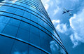 Glass curtain wall and aircraft against a blue sky Royalty Free Stock Photo