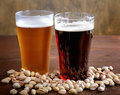 Glass of dark and light beer with nuts Royalty Free Stock Photo
