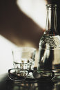 Glass decanter and glasses with a transparent liquid blurred on the table on the background of lighted wall Royalty Free Stock Image