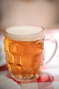 Glass dimpled beer mug cold in a condensing with foam or head shot at a creative angle Stock Photo