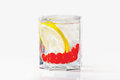 Glass of drink, ice, lemon and red cranberries Royalty Free Stock Photo