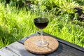 stock image of  Glass of dry red wine stands on a cork stand on the edge of the terrace surrounded by thick green vegetation