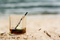 Glass filled with Irish whiskey on the sand beach
