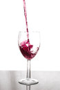 Glass filling with red wine Royalty Free Stock Photo