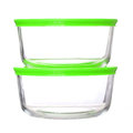 Glass food containers with green plastic lids on white background Royalty Free Stock Photos