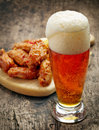 Glass of fresh beer and fried chicken wings Royalty Free Stock Photo