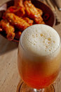 Glass of fresh beer and fried chicken wings on wooden table Stock Photo