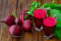 Glass of fresh beetroot juice with bets on wooden Royalty Free Stock Photo