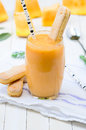 Glass of fresh cantaloupe smoothie with cookies and birch staraw Royalty Free Stock Photo