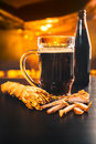 A glass of fresh dark beer with dried chicken and smoked cheese on a wooden table Royalty Free Stock Photo