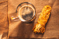 A glass of fresh dark beer with smoked cheese plait on sacking Royalty Free Stock Photo