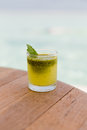 Glass of fresh juice or cocktail on table at beach Royalty Free Stock Photo