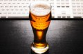 Glass fresh lager beer keyboard black table Stock Image