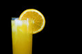Glass of fresh orange juice with ice and a slice of orange isolated on black background Royalty Free Stock Photo