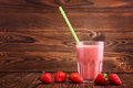 A glass of fresh and sweet smoothie on a brown wooden table. A few strawberries are near a full glass of drink. Royalty Free Stock Photo