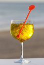 Glass of gin with spices yellow on a beach Royalty Free Stock Photo