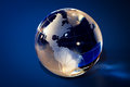 Glass globe in blue background Stock Photos
