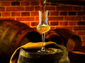 Glass of grappa glasses set in a cellar with barrels reserves Stock Photos