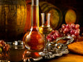 Glass of grappa glasses set in a cellar with barrels reserves Royalty Free Stock Image