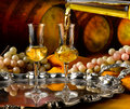 Glass of grappa glasses set in a cellar with barrels reserves Royalty Free Stock Photo