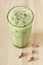 Glass of green tea latte decorated with dried rose on wooden background Stock Images