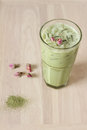 Glass of green tea latte with dried rose on wooden background decorated Royalty Free Stock Image