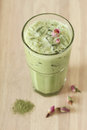 Glass of green tea latte with dried rose on wooden background decorated Royalty Free Stock Photos