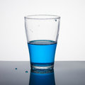 Glass half full of blue liquid on light background Stock Photo