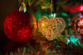 Glass heart christmas tree decoration ornament closeup of a with colorful lights branches and sparkling decorations in the Royalty Free Stock Photo