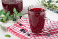 Glass of honeysuckle kissel berries in a and a jug Stock Photo