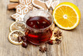 Glass of hot steaming tea among christmas decorations on wooden table Stock Image