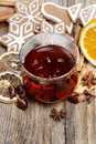 Glass of hot steaming tea among christmas decorations on wooden table Royalty Free Stock Photography