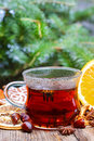 Glass of hot steaming tea among christmas decorations on wooden table Stock Photography