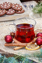Glass of hot steaming tea among christmas decorations on wooden table Stock Photo