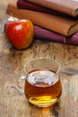 Glass of hot steaming tea on wooden table pile books and red single apple in the background Stock Images