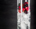 Glass of ice with berry gooseberries red black currants and water. Refreshing cocktail. Summer drink. Royalty Free Stock Photo