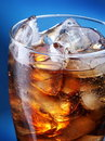 Glass of ice cola on a blue Royalty Free Stock Images
