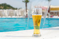 Glass of ice cold beer at the edge of a pool Royalty Free Stock Photo