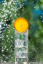 Glass with ice and sparkling water, with a slice of orange, surrounded by splashes and drops of water, concept Royalty Free Stock Photo