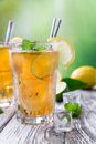 Glass of ice tea with cubes on wooden table Stock Images